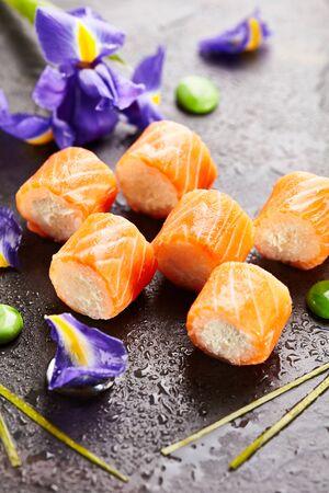 japanese sake: Philadelphia Maki Sushi made of Cream Cheese and Rice inside. Salmon outside. Japanese Cuisine and Natural Flower Concept Foto de archivo