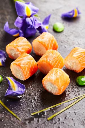 japanese sake: Philadelphia Maki Sushi hecho de queso crema y arroz en el interior. Salmón exterior. Cocina japonesa y concepto natural de la flor Foto de archivo