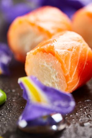 adentro y afuera: Philadelphia Maki Sushi hecho de queso crema y arroz en el interior. Salmón exterior. Cocina japonesa y concepto natural de la flor Foto de archivo