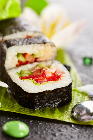 vegetarian cuisine: Vegetarian Maki Sushi - Roll made of Tomato, Cucumber, Bell Pepper and Salad Leaf inside. Japanese Cuisine and Natural FLower Concept