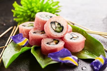 Tuna Maki Sushi - Rouleau de l'anguille fumée et du concombre à l'intérieur. Thon cru frais à l'extérieur. Cuisine japonaise et concept de fleur naturelle Banque d'images