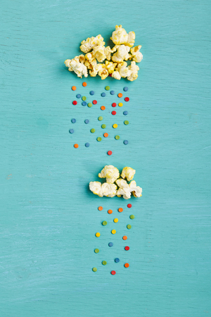 Weather Concept - Top View of Creative Popcorn Clouds with Colorful Sweet Rain on Blue Background. Minimal Concept. Flat Lay