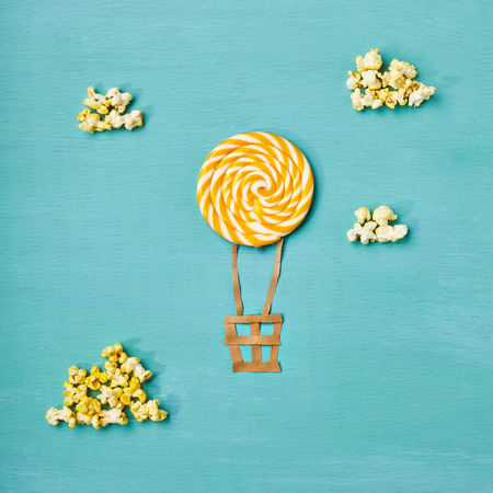 Creative Travel Concept - Top View Sweet Candy Air Balloons and Popcorn Clouds on Blue Background. Minimal Travel and Food Fun Concept. Flat Lay Stock Photo