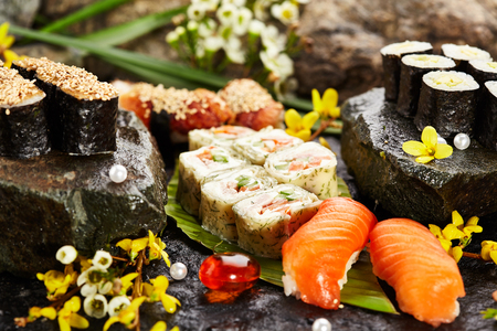 sushi restaurant: Japanese Sushi Set - Various Maki Sushi Roll and Nigiri Sushi. Japanese Cuisine and Natural Flower Concept Stock Photo