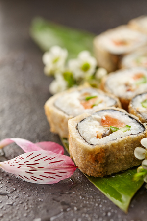 Japanese Sushi Food and Natural Flower Concept. Tempura Maki Sushi - Deep Fried Sushi Roll made of Fresh Raw Salmon, Smoked Eel, Cucumber and Cream Cheese inside. Sushi Served on Banana Leaf. Stock Photo
