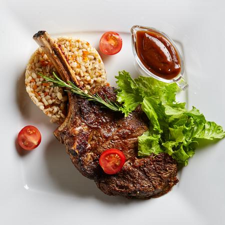 Gegrilltes Restaurant Food - Kalbfleisch Rippen Grill mit Beilage, Sauce und Rosmarin auf schwarzen Stein Hintergrund Standard-Bild - 73049487
