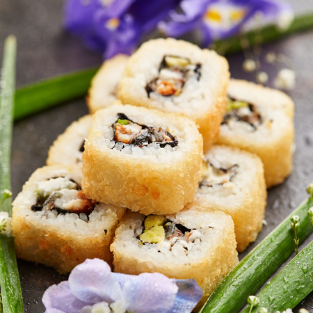 sake: Tempura Maki Sushi - Deep Fried Sushi Roll made of Smoked Eel, Avocado and Cream Cheese inside. Japanese Sushi Food and Natural Flower Concept