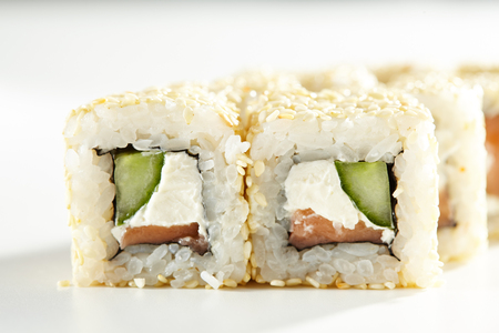 adentro y afuera: Japanese Sushi Food - Sushi Roll with Salmon, Cucumber and Cream Cheese inside. Sesame outside. Maki Sushi on White Background Foto de archivo