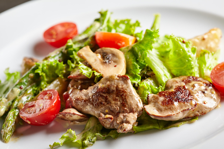higado de pollo: Restaurant and Gourmet Food - Warm Chicken Liver Salad with Mushrooms, Asparagus and Cherry Tomato. Foto de archivo