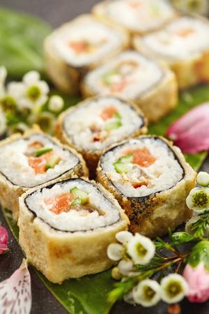 sake: Comida japonesa del sushi y concepto natural de la flor. Tempura Maki Sushi - Deep Fried Sushi Roll de salmón fresco, anguila ahumada, pepino y queso crema dentro. Sushi servido en hoja de plátano.