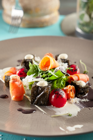 Restaurant Salad Food - Black Caesar Salad with Smoked Salmon. Gourmet Restaurant Salad Menu. Salad Garnished with Rucola, Salad Leaves and Vegetables Stock Photo