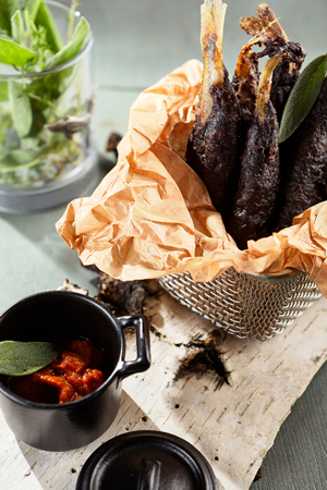 Restaurant Fish Menu - Crispy Black Fried Smelt Fish with Hot Spicy Sauce. Traditional Russian Fish Dish Served on Birch Bark. Rustic Style