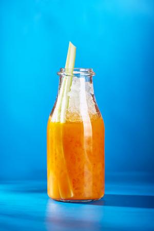 crushing: Summer Lemonade - Sea Buckthorn Lemonade decorated with Celery. Lemonade Glass Bottle on Bright Blue Background