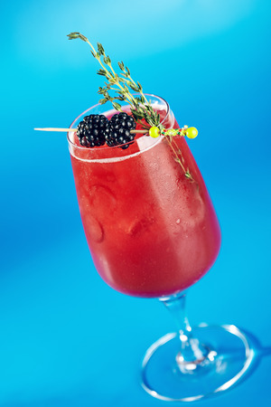 water cooler: Berry Cocktails for Holiday on Blue Background. Drink Dressed with Blackberry and Thyme