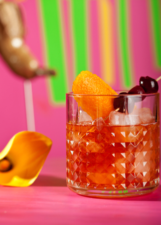 sweet vermouth: Alcohol Cocktail - Old Fashioned Cocktail or Manhattan Cocktail. Bourbon, Cane Sugar, Bitter and Orange Peel. Cocktail with Fruit and Flower on Pink Background
