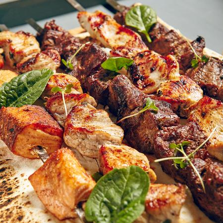 Kip, zalm en vlees Shish Kebabs op perkament met sauzen Stockfoto