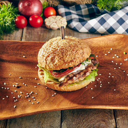 Burger Grill Restaurant Menu - Delicious Bacon Burger on Wood Plate. Rustic Wooden Table and Ingredients on Background Stock Photo