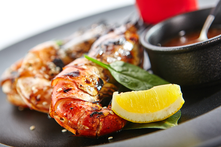 grill: Teppanyaki Japanese and Korean Grill Food - 68 Shrimp Grill with fresh herbs and sauces on black plate