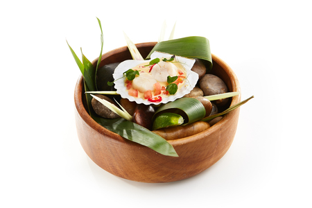 carnes y verduras: Sea scallop in cream with tomatoes and chili pepper sprinkled with fresh herbs served in shell on stones in wooden bowl. Gastronomic restaurant menu