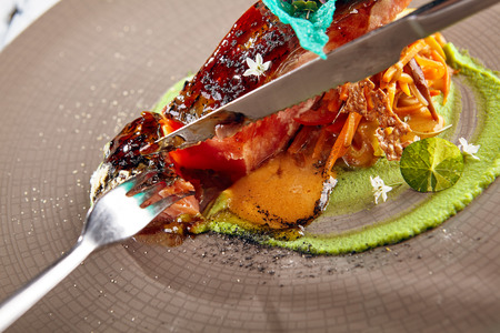 Fork and knife with slice of salmon sous vide with julienne of stewed vegetables and fresh herbs on decorated ceramic dish. Gastronomic restaurant menu