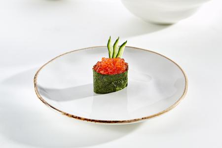 Gunkan sushi with red caviar ikura and cucumber on white plate with gold border. Pan Asian restaurant menu