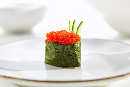 Gunkan sushi with tobiko and cucumber on  white plate with gold border. Pan Asian restaurant menu