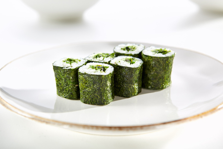 tekka: Maki rolls with seaweed with Hiashi wakame served on white flat plate. Asian menu for gourmets in luxury restaurant