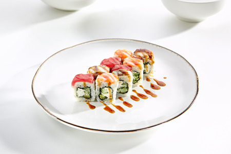 tekka: Rainbow sushi rolls with salmon, tuna, eel, Philadelphia cheese and cucumber served on white flat plate. Asian menu for gourmets in luxury restaurant