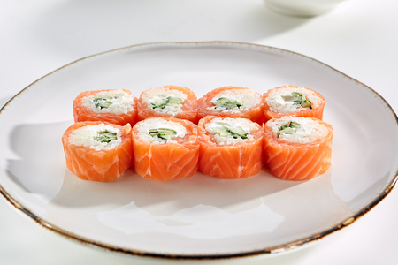 tekka: Miyazaki rolls with salmon, cucumber and sesame seeds and Philadelphia cheese served on white flat plate. Asian menu for gourmets in luxury restaurant