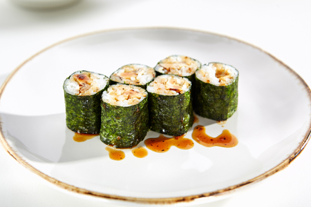 tekka: Maki rolls with tamagoyaki served on white flat plate. Asian menu for gourmets in luxury restaurant Stock Photo