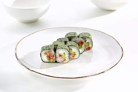 tekka: Kimasu rolls with shrimp, eel, avocado, tobiko caviar and Philadelphia cheese served on white flat plate. Asian menu for gourmets in luxury restaurant