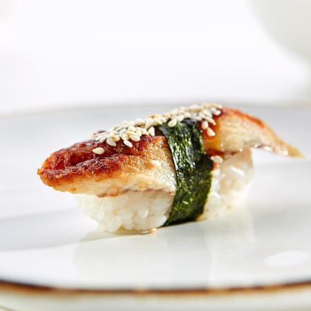 Nigiri sushi with eel and sesame on white plate with gold border. Pan Asian restaurant menu