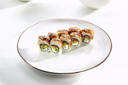 tekka: Kanada sushi rolls with salmon, eel, Philadelphia cheese, avocado and cucumber served on white flat plate. Asian menu for gourmets in luxury restaurant