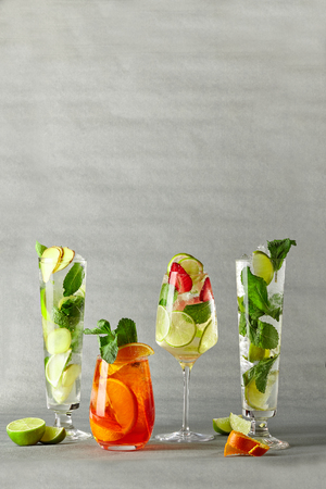Mojito and aperol syringe with lime lemon ginger orange and strawberries in glass glasses Stock Photo