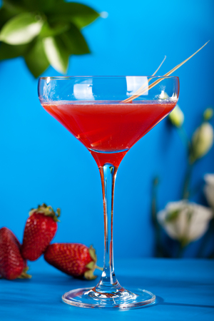 Summer Cocktail - Cosmopolitan Cocktail with Fresh Strawberry on Blue Background.