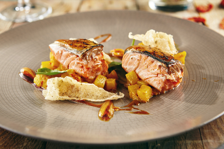 Menu of gastronomic restaurant. Salmon sous-vide with pineapple ragout with fresh herbs on ceramic plate