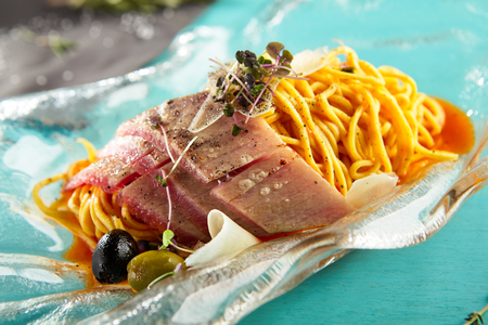 caper: Pasta with tuna and tomatoes with olive greens and spices on glass plate. Gastronomic restaurant menu