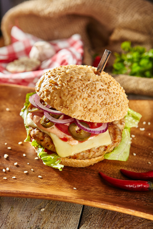 Burger Grill Restaurant Menu - Delicious Spicy Chili Burger on Wood Plate. Rustic Wooden Table and Ingredients on Background