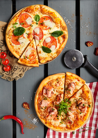 pizza cutter: Italian Pizza Restaurant Menu - Margarita and Salmon Pizza. Pizza Dinner. Top View
