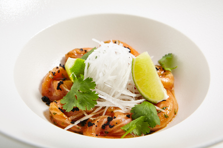 Snack in restaurant of pan-Asian cuisine - slices of chilled salmon in spicy dressing with parsley and lime slices lie on white plate Stock Photo