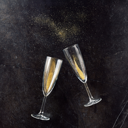 Merry Christmas and Happy New Year greeting card with champagne glass made of glitter sand on black slate background Standard-Bild
