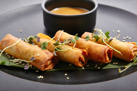 vietnamese ethnicity: Spring rolls - fried Vietnamese rolls of rice edible paper on black matte plate next to cup with sauce. Pan-Asian menu of restaurant.