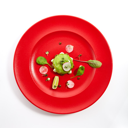 Pan-Asian menu in restaurant - dish called Kamchatka ball - crab inside outside avocado with fruit and vegetable slices sprinkled with fresh herbs on red plate. Top View Stock Photo