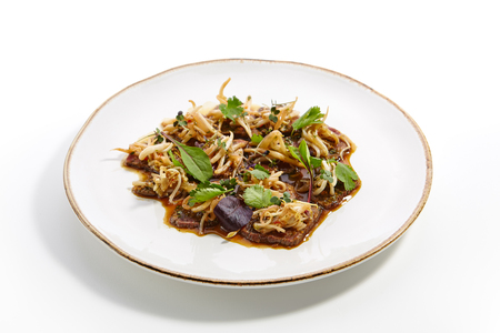 Specialty in restaurant of Asian cuisine - Tataki from beef with sprouted soybean sprinkled with fresh herbs lie on white plate