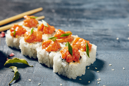 Japanese sushi roll topped with spicy salmon slice on dark grunge background