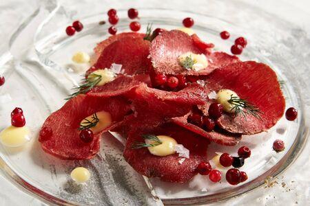 carnes: Finas rodajas de carne de venado de ternera delicatessen en placa plana transparente sobre fondo blanco copyspace rústico