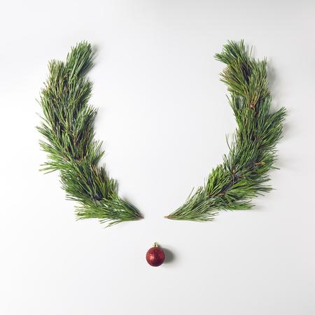 松の枝とクリスマスの装飾で作られたトナカイの顔。メリー クリスマスと新年あけましておめでとうございます概念。フラット レイアウト