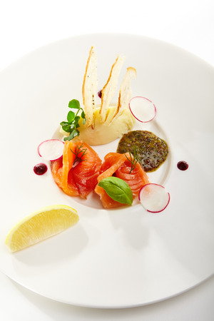 Salmon with mashed potatoes and mustard dressing with greens and slices of radishes and piece of orange in white bowl on isolated white background. Gastronomic restaurant menu