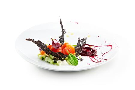 Salmón con caviar, verduras y pepino en salsa cremosa y hojas de albahaca en un plato blanco sobre un fondo aislado. Menú gastronómico del restaurante
