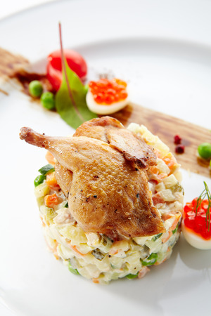 Olivier Salad or Russian Salad with Roasted Quail and Red Caviar on White Plate Isolated. Diced Potatoes, Carrots, Brined, Dill, Pickles, Green, Peas, Eggs, Onions, Mayonnaise and Spices Stock Photo